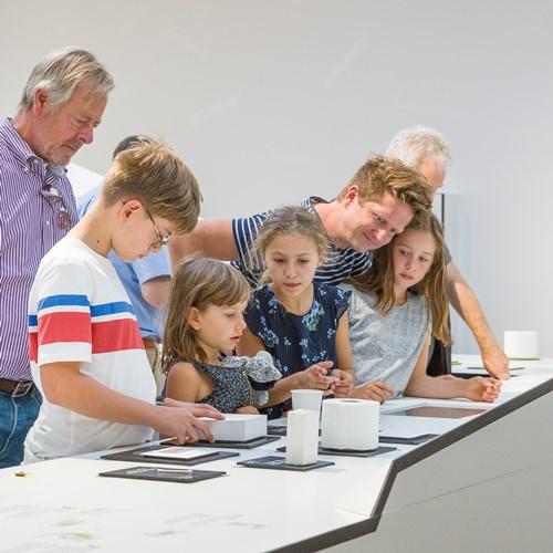 Besucher stehen am Ausstellungsdisplay